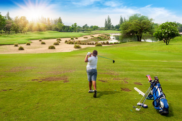 13-year-old Asian boy playing golf on a golf course in the sun - Image