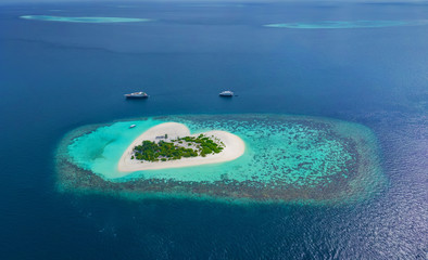 Aerial of beautiful heart shaped tropical island in blue sea at Maldives paradise panoramic background