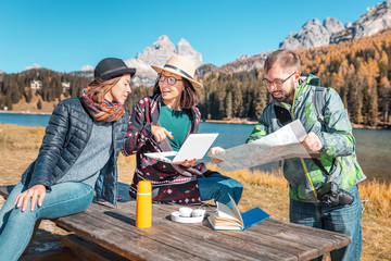 A group of friends with a map and a laptop in a mountain reserve on the shore of a beautiful lake are looking for a good hotel to book on the Internet to continue the adventure