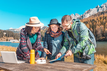 Three happy friends with notebook and laptop in nature park at the background of a mountain lake in Alps