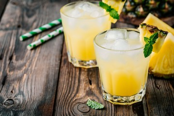 Foto op Canvas Sap Fresh pineapple juice in two glasses with ice and mint on dark rustic background