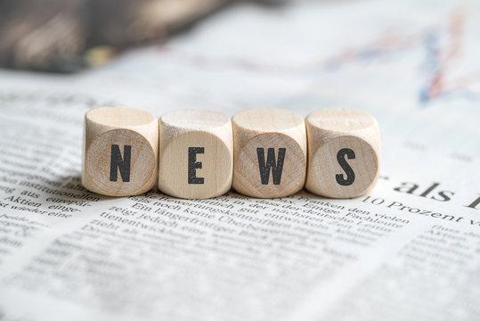"""Würfel mit dem Wort """"NEWS"""" auf einer Zeitung"""