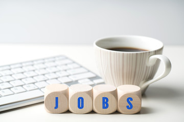 Würfel mit Aufschrift JOBS vor einer Tastatur