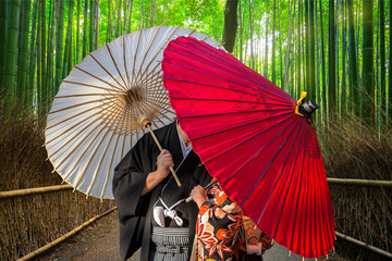 Couple with traditional japanese umbrellas posing at bamboo forest in Arashiyama