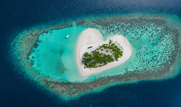 Drone Aerial view of beautiful tropical heart shaped island among blue sea water at Maldives paradise with boat on background