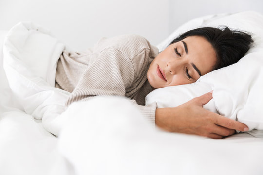 Photo of middle-aged woman 30s sleeping, while lying in bed with white linen at home