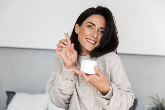 Image of smiling woman 30s holding jar with face cream, in modern bright room