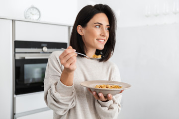 Image of adult woman 30s eating corn flakes on breakfast, while standing in modern kitchen at home