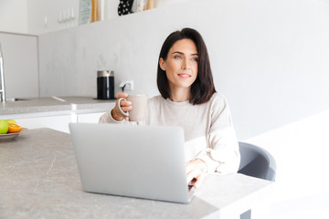 Image of smiling woman 30s working on laptop, while sitting over white wall in bright room