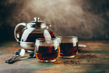 Transparent glass teapot black tea and glass cups