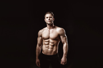 Muscular model young man on dark background. Fashion portrait of strong brutal guy with trendy hairstyle. Sexy naked torso, six pack abs. Male flexing his muscles. Sport workout bodybuilding concept. Wall mural