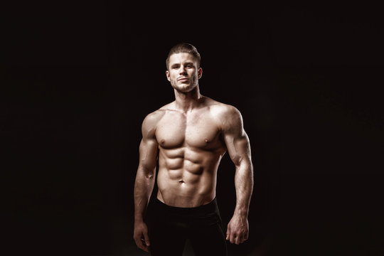 Muscular model young man on dark background. Fashion portrait of strong brutal guy with trendy hairstyle. Sexy naked torso, six pack abs. Male flexing his muscles. Sport workout bodybuilding concept.