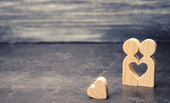 A miniature couple in love and a heart near them. The concept of family problems and loss of feelings for your loved one. Consultation family psychologist. Rupture / divorce. Selective focus