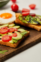 selective focus of cutting board with toasts, scrambled egg, cherry tomatoes and avocado on white background