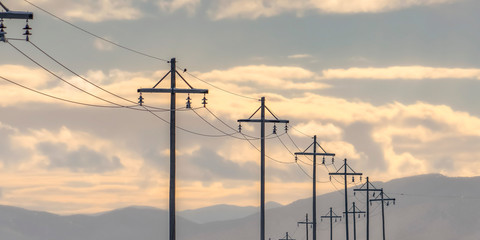 Row of electricity posts against mountain and sky