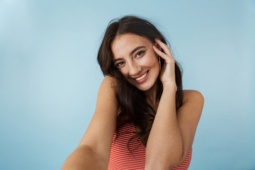 Woman posing isolated over blue wall background.