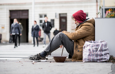 Homeless beggar man sitting outdoors in city asking for money donation. Wall mural