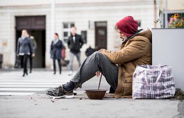 Homeless beggar man sitting outdoors in city asking for money donation. Fototapete