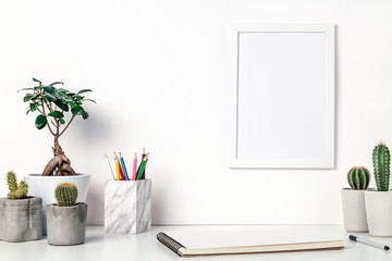 Desk at the white empty wall. Copy space. Place for text. Scandinavian style. White empty frame mockup. Cactuses, bonsai, colored pencils in a marble container and an open notebook