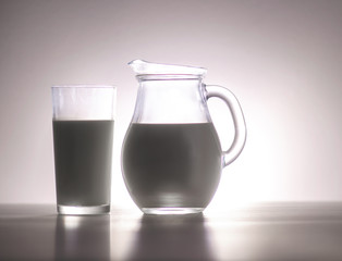 Natural whole milk in a jug and a glass on a white background closeup