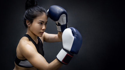 Deurstickers Vechtsport Young Asian woman boxer posing uppercut with blue boxing gloves in fitness gym. Female boxing class. Martial arts concepts