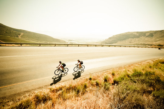 Wide angle view of a road cyclist riding on a tarmac road in the country side with a great view over the farmlands of the western cape in south africa