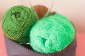 colorful skeins of yarn and knitting needles in a box