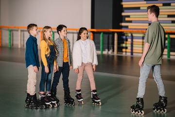 Pretty smiling children in roller skates attentively listening to trainer instructions