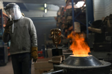 A foundry worker stands next to a British Academy of Film and Television Awards (BAFTA) mask as after placing the mask next to the furnace to be photographed at a foundry in west London