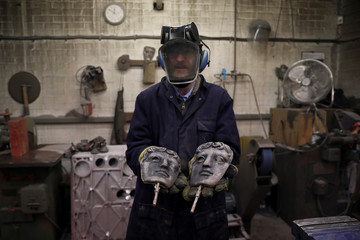 A foundry worker poses for a photograph with a British Academy of Film and Television Awards (BAFTA) masks at a foundry in west London