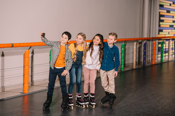 Little boy making selfie with friends while skating together