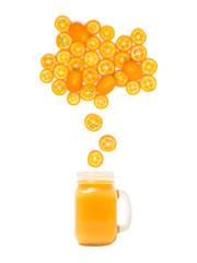 glass with fresh kumquat juice is standing under many kumquat slices on white background