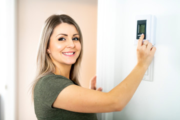 A nice Woman programming temperature inside home