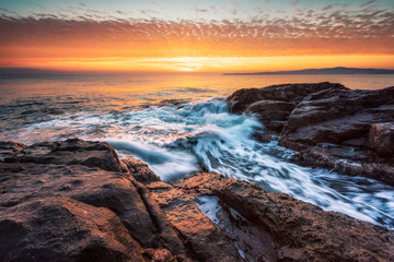 Stormy sea with colorful sunrise sky at the rocky coastline of the Black Sea