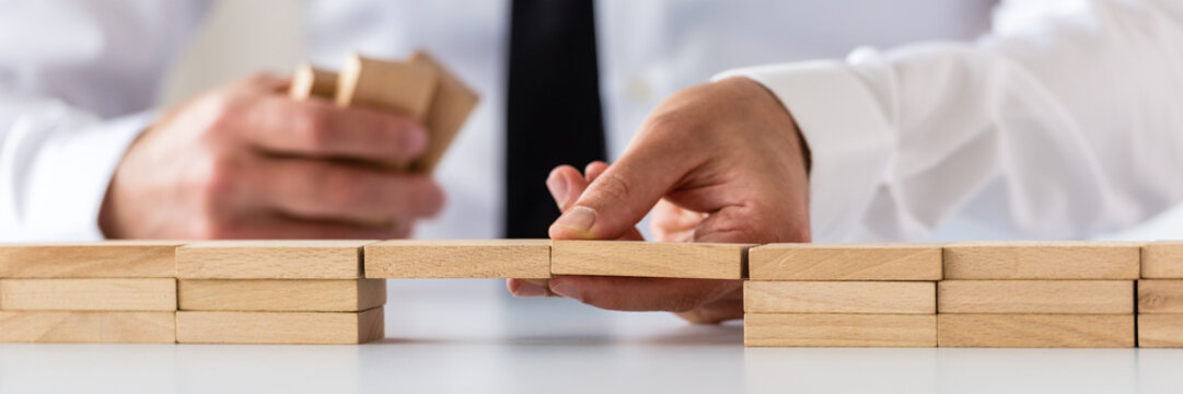 Wide view image of businessman making a bridge of wooden pegs