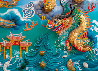 The close up of the colorful statue of  chinese dragon on the blue wall.Beautiful statue of dragon carved around temple pole in Chinese public temple.