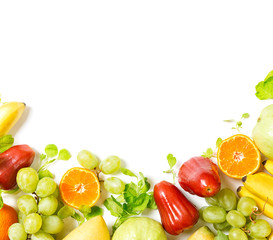 flat lay top view tropical fruits frame background: grape, rose apple, orange, spinach, mango, pear, guava and banana. Healthy drink ingredients. Vegetarian, vegan food concept. Detox. Text space