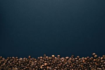 Coffee beans below on black background.