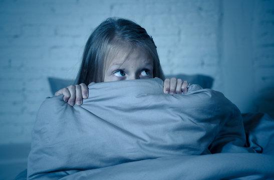 Sleepless cute girl in fear at night hiding behind the blanket afraid of dark and monsters