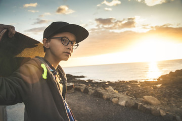 Handsome child with glasses and skater black hat looking the ocean at the sunset with skateboard on the shoulders.  Teen enjoying outdoors in a beautiful holiday summer day. Trendy young teenager