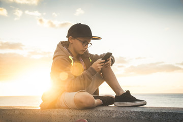 Handsome child with glasses and skater black hat sitting play with cellphone.Teen relaxing with phone enjoying outdoors at the sunset. Outdoor chatting with internet friends online near the ocean
