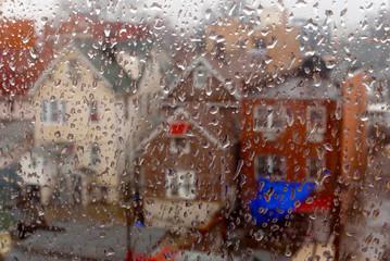 Row of houses seen through a window with rain drops