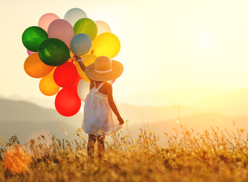 . happy child with balloons at sunset in summer