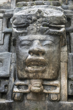 Close up shot of the Olmec style stone mask on the Mayan temple of Lamanai in Belize.
