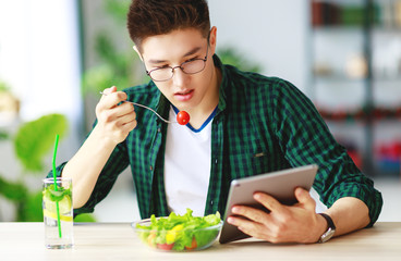 healthy eating. happy young asian man eating salad with phone and tablet pc in  morning .
