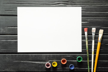 The tools of the artist, brushes, paints and canvas are not dark wooden background.