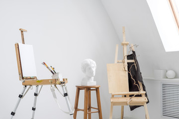 White and bright studio with a window. Workspace of the artist. Easel, canvases and plaster figures for learning to draw.