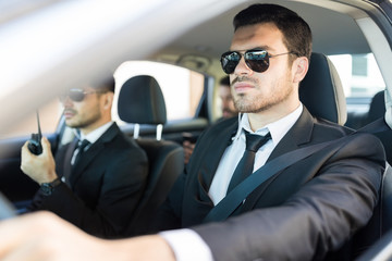 Man In Suit Providing Security To Boss During Journey