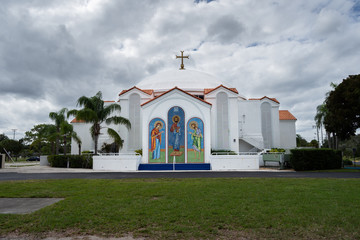 wide angle shot of beautiful white church building on a cloudy day