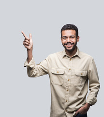 Portrait of handsome smiling young man pointing up. Laughing joyful cheerful men isolated studio shot